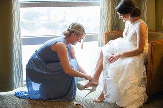 maid-of-honor-helping-bride-into-sparkling-heel