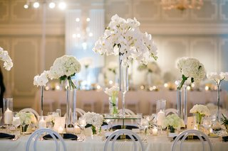 wedding-reception-flower-centerpieces-white-orchid-hydrangea-in-tall-vases-white-chairs