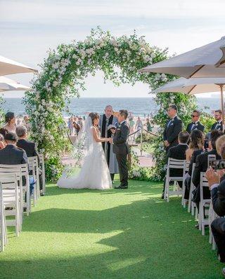 wedding-ceremony-on-grass-lawn-near-beach-ocean-san-diego-coronado-island-umbrella-greenery-arch