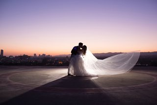 groom-dips-bride-veil-blowing-in-wind-rooftop-picture-of-newlyweds-at-sunset