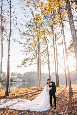 bride-in-mock-turtleneck-wedding-dress-cathedral-veil-groom-in-forest-sun-fall-winter-trees-lake