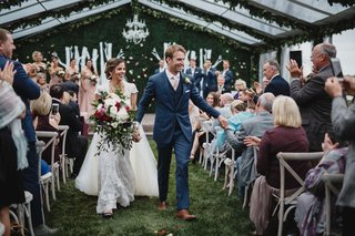 wedding-ceremony-greenery-clear-top-tent-guests-in-vineyard-chairs-high-five-happy-couple-newlyweds