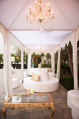 white-ottoman-settees-and-benches-in-cabana-with-chandelier-and-gold-coffee-table
