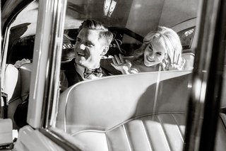 black-and-white-photo-of-the-newlywed-couple-waves-goodbye-to-guests-from-their-classic-getaway-car
