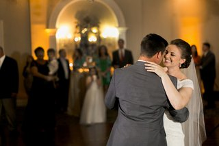 bride-in-an-off-the-shoulder-sottero-and-midgley-lace-dress-veil-dances-with-groom-in-grey-suit