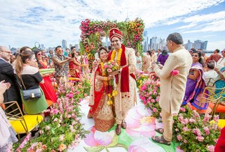 indian-american-groom-japanese-bride-multicultural-wedding-flower-print-aisle-guests-colored-chairs