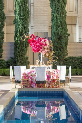 floral-table-linen-white-chair-sleeve-pink-rose-centerpiece-arrangement-reflected-in-pool