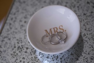 wedding-ring-halo-diamond-engagement-ring-eternity-band-in-white-ceramic-dish-with-mrs-in-gold