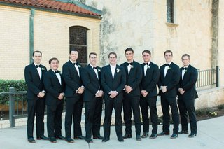 groom-in-black-suit-with-white-bow-tie-and-groomsmen-in-black-suits-with-black-bow-ties-cowboy-boot