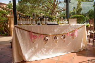 wedding-shower-perfume-station-with-banner-of-couples-initials-and-hearts-on-triangle-flags