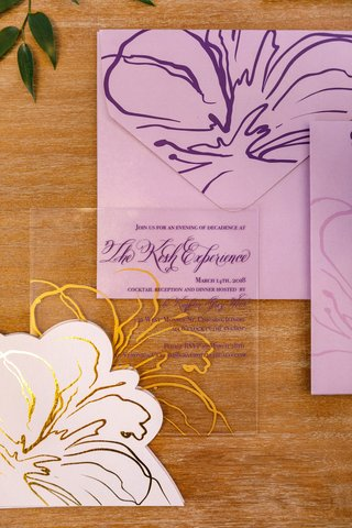 purple-lettering-gold-flower-purple-envelope-see-through-clear-lucite-acrylic-invite-on-wood-table