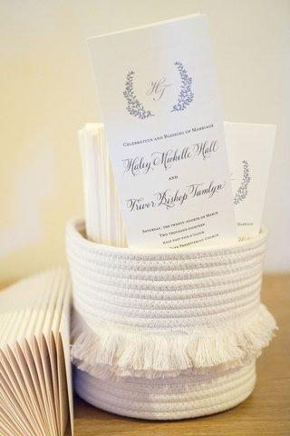 wedding-ceremony-programs-monogram-calligraphy-in-white-robe-basket-with-tassel-fringe-in-middle