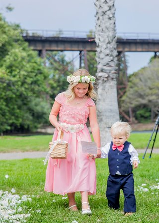 flower-girl-in-pink-dress-with-flower-sash-belt-basket-flower-crown-ring-bearer-in-vest-pink-bow-tie