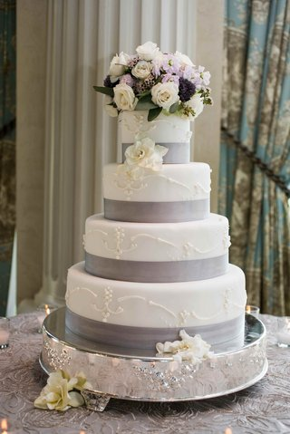 white-cake-with-ribbon-band-and-fresh-flowers-on-top