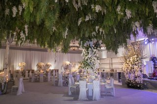 wedding-reception-ballroom-violet-lighting-greenery-overhead-white-flowers-silver-decor-bar-band