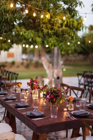 destination-wedding-small-arrangements-with-dark-pink-flowers-dark-wood-tables