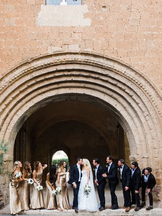 bride-and-groom-kiss-in-umbria-italy-with-bridesmaids-gold-champagne-wedding-dresses-groomsmen-suits