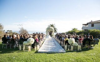 whitewash-wood-plank-wood-aisle-with-hurricane-vases-candles-white-bouquets-of-flowers-arch-ocean