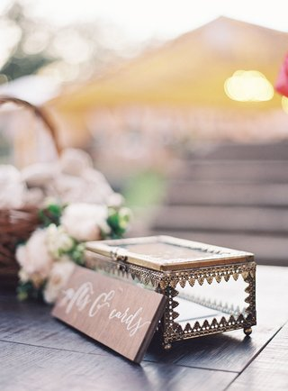 wedding-card-and-gift-box-clear-jewelry-box-with-wood-sign-next-to-flowers-in-basket