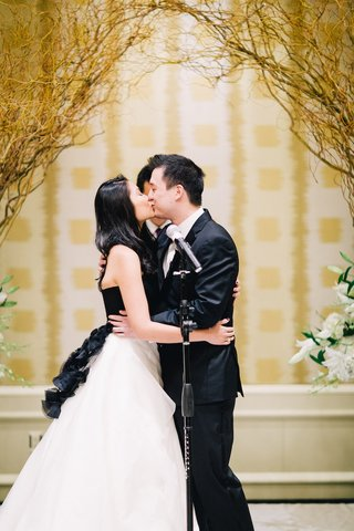 bride-in-a-strapless-vera-wang-gown-with-a-black-bodice-and-white-skirt-kisses-groom-in-black-tuxedo