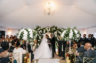 wedding-ceremony-african-american-couple-tented-structure-chandelier-greenery-white-orchid-flowers