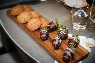 wedding-dessert-wood-cutting-board-with-chocolate-chip-cookie-desserts-and-chocolate-dipped-berries