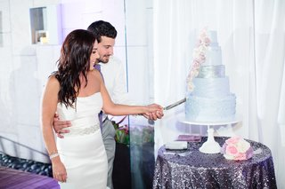 bride-in-a-strapless-vera-wang-dress-beaded-sash-and-groom-in-white-shirt-grey-pants-cut-cake