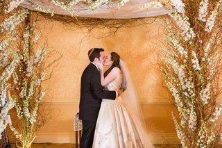 newlyweds-share-first-kiss-husband-wife-jewish-wedding-chuppah-yarmulke-ivory-wedding-dress-white