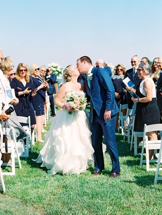 wedding-outdoors-grass-lawn-white-chairs-for-guests-groom-in-blue-suit-bride-in-strapless-dress-kiss