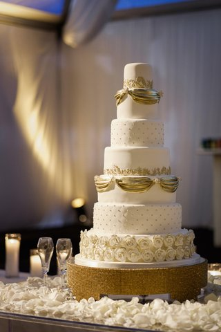 white-wedding-cake-with-golden-ribbons-pearls-and-gold-rimmed-sugar-roses