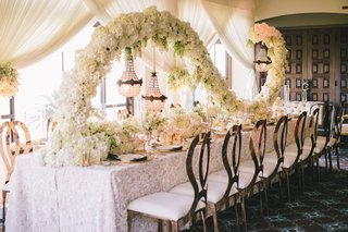 long-wedding-reception-table-with-swirl-centerpiece-of-white-hydrangeas-lilacs-stephanotis-tulips
