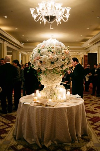 round-table-with-guest-book-and-tall-flower-arrangement-enrobed-in-white-and-pink-flowers