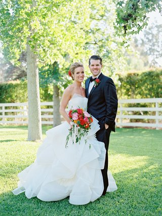 bride-in-strapless-vera-wang-wedding-dress-with-vibrant-pink-and-red-bouquet-with-groom-in-tuxedo