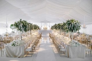 white-tented-wedding-reception-space-tall-tree-centerpieces-long-kings-tables-round-tables-around