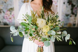 bride-in-boho-dress-holding-loose-bouquet-seasonal-greenery-with-pale-yellow-ranunculus-and-dahlia