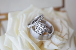 wedding-rings-engagement-ring-in-halo-setting-matching-wedding-band-with-mens-ring-on-white-rose
