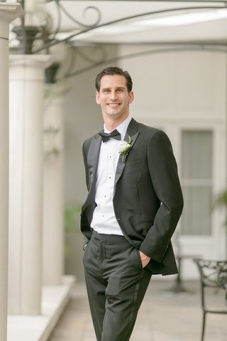 groom-smiling-at-camera-with-tuxedo-pants-bow-tie-and-white-boutonniere