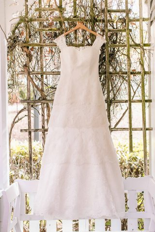 a-beautiful-lace-wedding-dress-with-four-tiers-and-straps-hangs-up