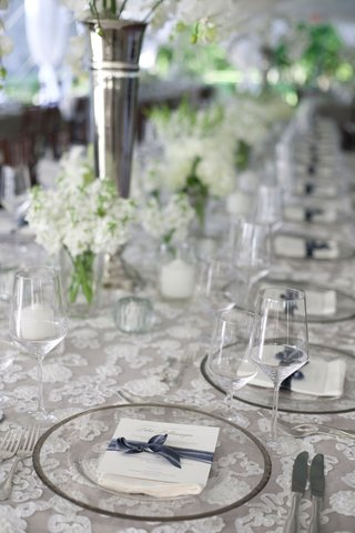 long-table-with-white-lace-table-linens-and-clear-glass-plates-glasses-white-and-gray-place-cards