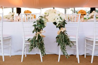 beach-tented-wedding-reception-with-newlyweds-chairs-joined-by-greenery-white-roses-hydrangeas