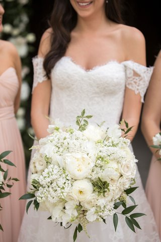 bride-in-lace-off-shoulder-gown-holding-white-rose-astilbe-sweet-pea-and-ranunculus-flowers