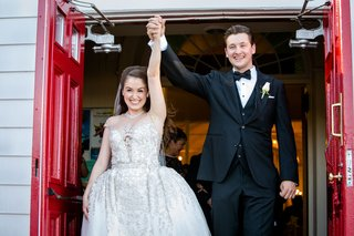bride-in-wedding-dress-ball-gown-from-kleinfeld-bridal-cap-sleeves-jewels-bow-tie-on-groom-hands-up