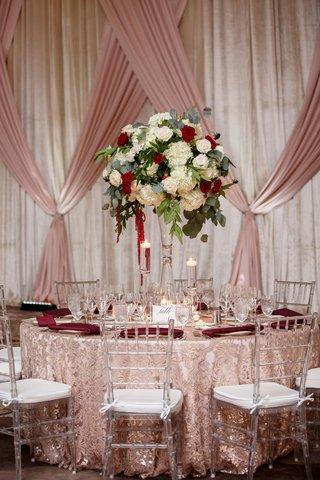 wedding-reception-clear-chair-texture-linen-tall-centerpiece-greenery-white-hydrangea-rose-red