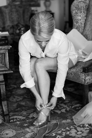 black-and-white-photo-of-bride-putting-on-heels