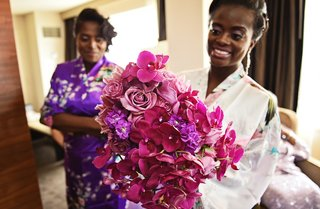 bride-in-robe-holds-bouquet-of-magenta-orchids-light-purple-roses