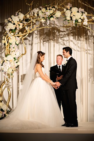 bride-and-groom-married-under-gold-branch-archway