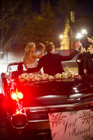bride-and-groom-drive-away-from-reception-on-top-of-convertible