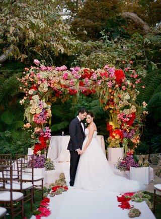 bride-and-groom-hold-hands-under-colorful-jewish-wedding-chuppah-at-hotel-bel-air-swan-lake