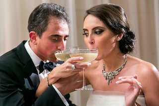 bride-groom-intertwine-arms-sip-champagne-wedding-classic-drink-fun-traditions-big-coupe-glasses