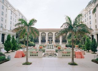 wedding-reception-cocktail-hour-palm-trees-coral-linens-and-flowers-the-breakers-palm-beach